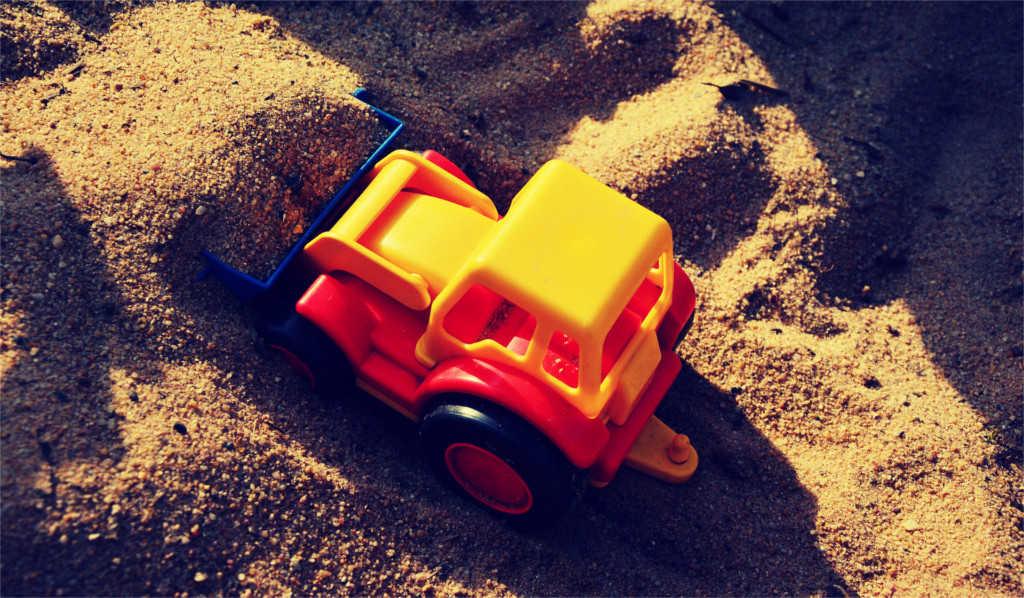 Ein Spielzeugbagger im Sand