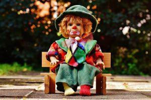 ein Clown sitzt auf einer Bank