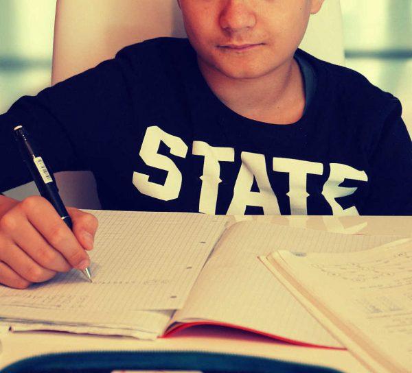 Ein Jugendlicher sitzt schreibend am Tisch