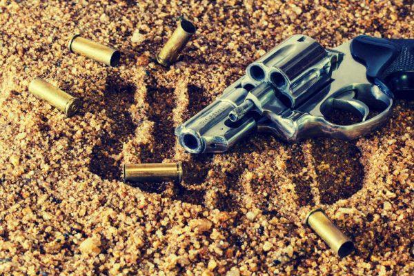 Eine Pistole, Kugeln und Fußabdrücke