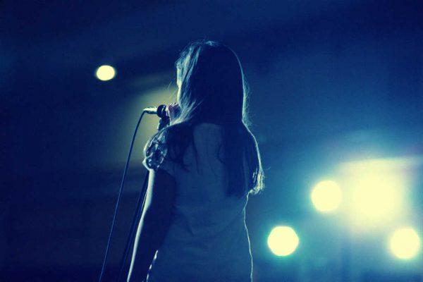 Kind auf einer Bühne mit Microphon