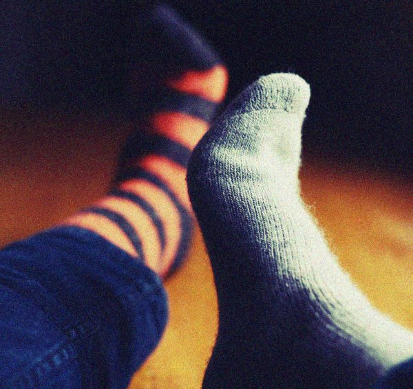 verschiedene Socken an Füßen