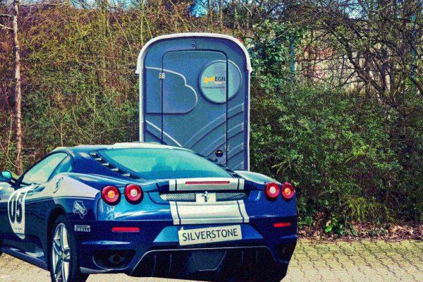 Ein Sportwagen vor einer Toilette